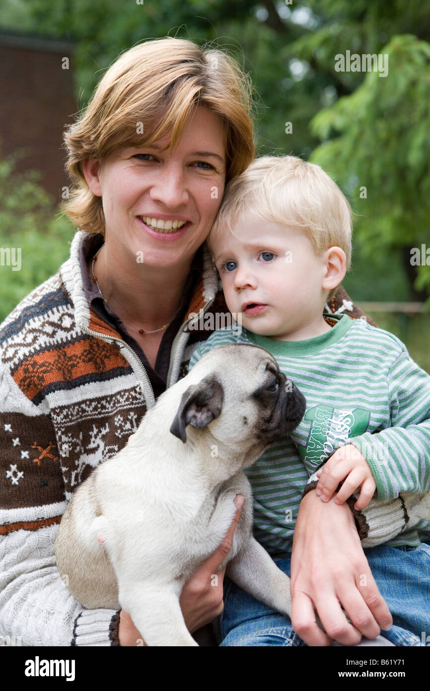 Young woman, 30+, child, boy, 2, dog, pug, puppy, portrait - Stock Image