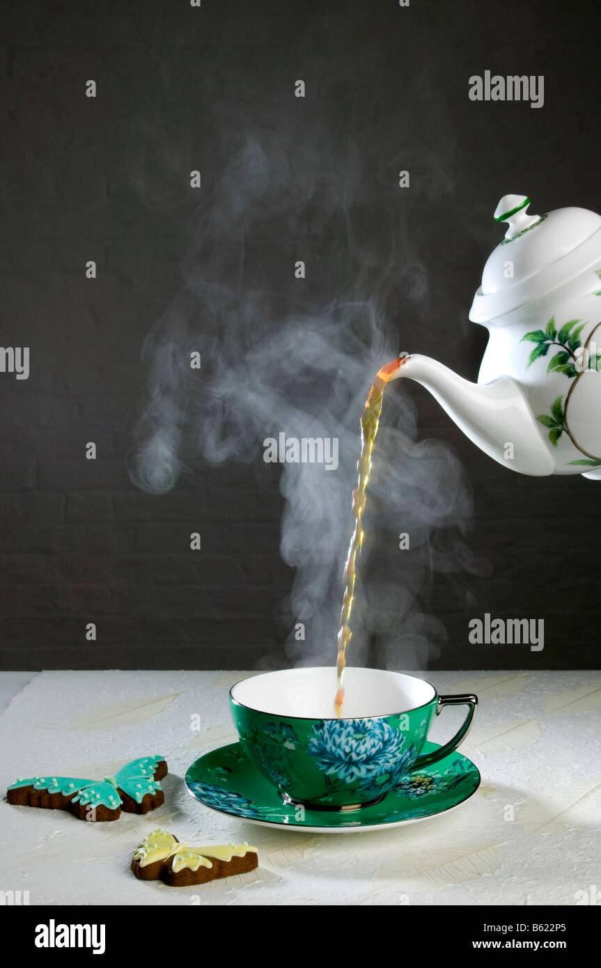 Pouring tea from a China tea pot - Stock Image
