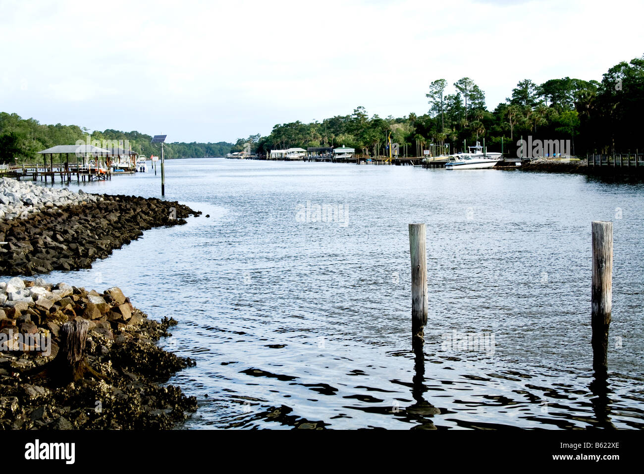 Two wooden posts on the rocky shore of the Intracoastal waterway in Florida - Stock Image