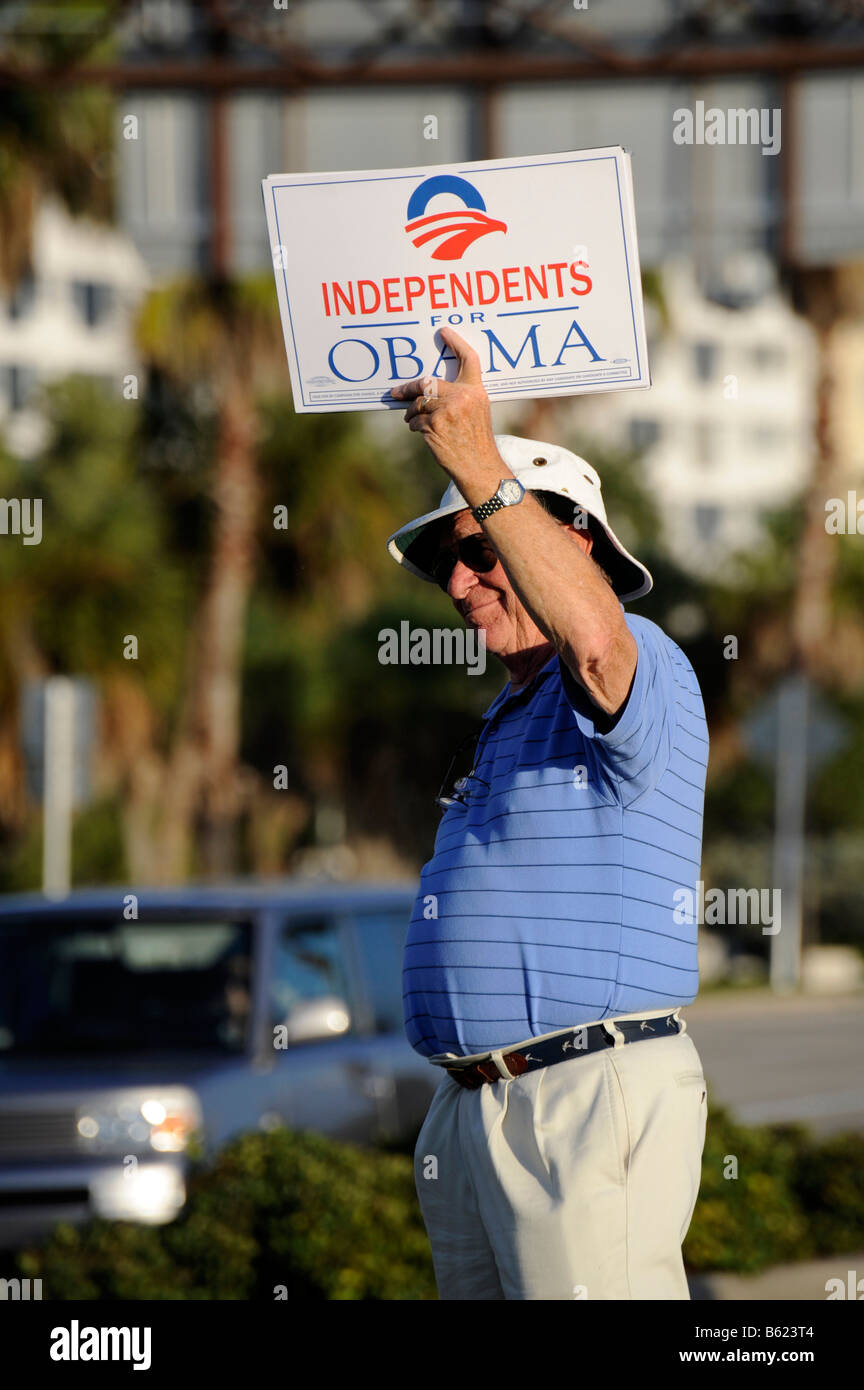 Male senior citizen supporter shows sign for Barack Obama for President on busy road - Stock Image