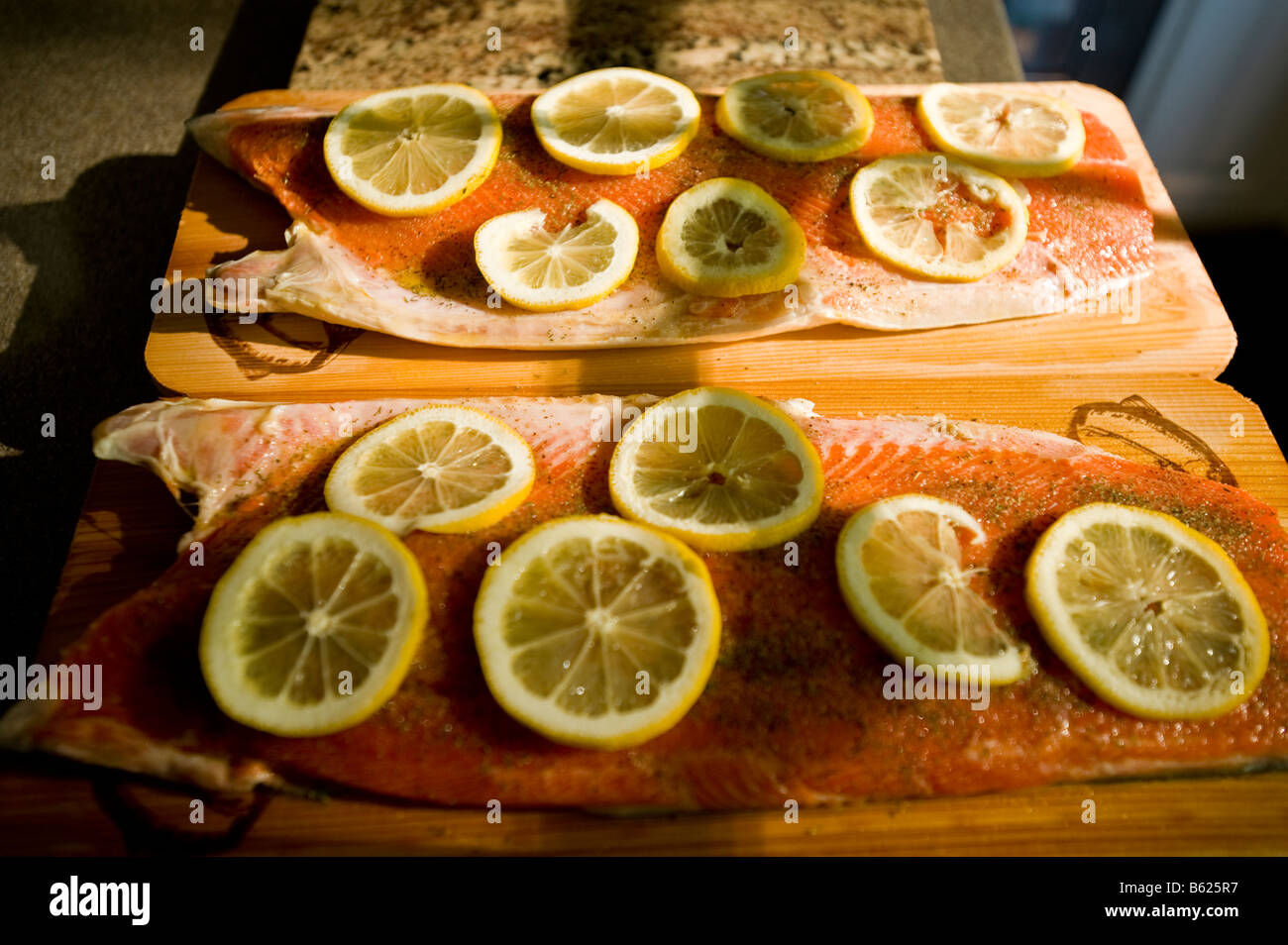 Two halves of a sockeye salmon are seasoned and prepared for the grill on soaked cedar planks - Stock Image