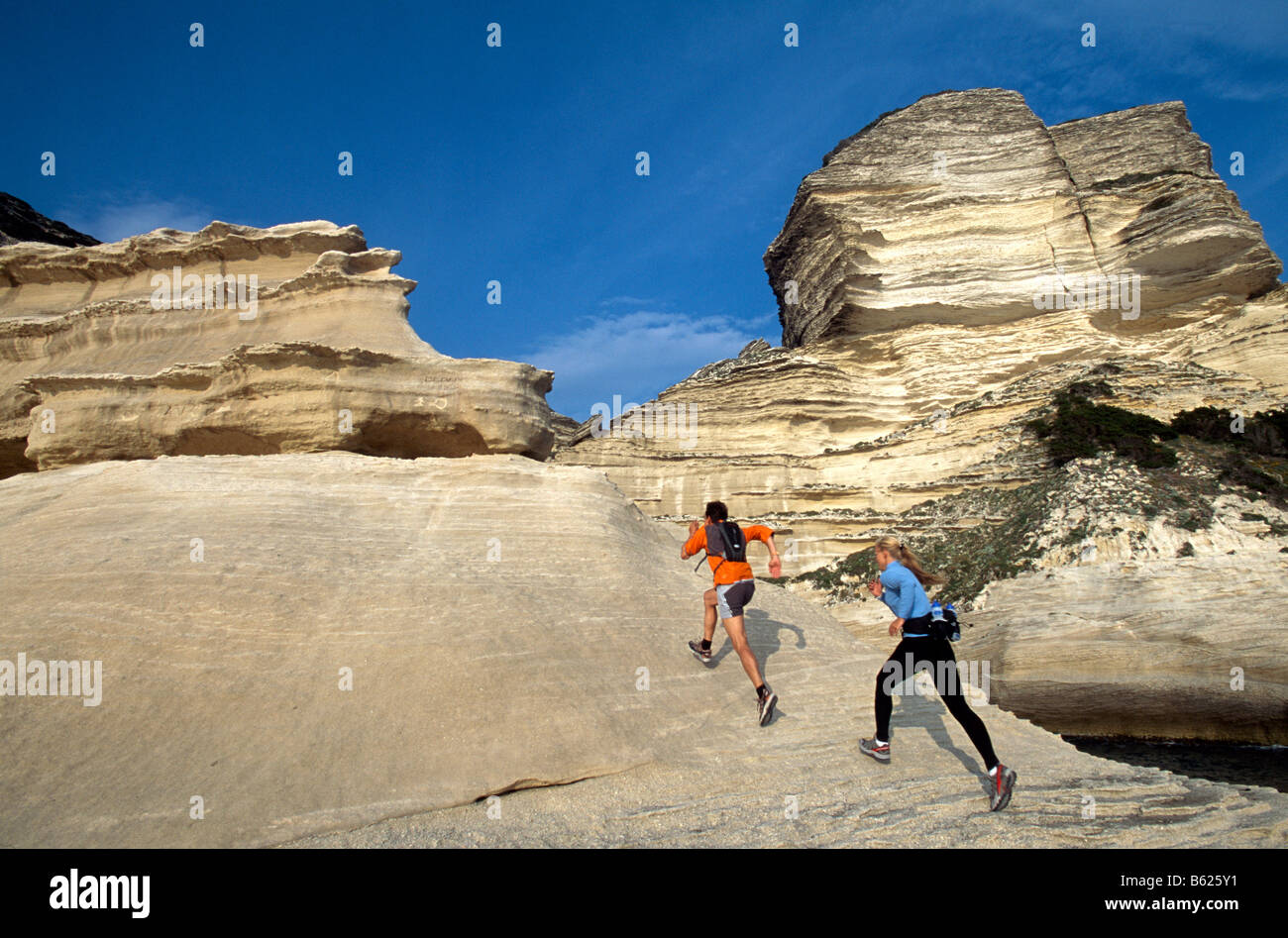 A man and woman participating in Running, Crossrunning, steep coast, Santa Manza, Bonifacio, Corsica, France, Europe - Stock Image
