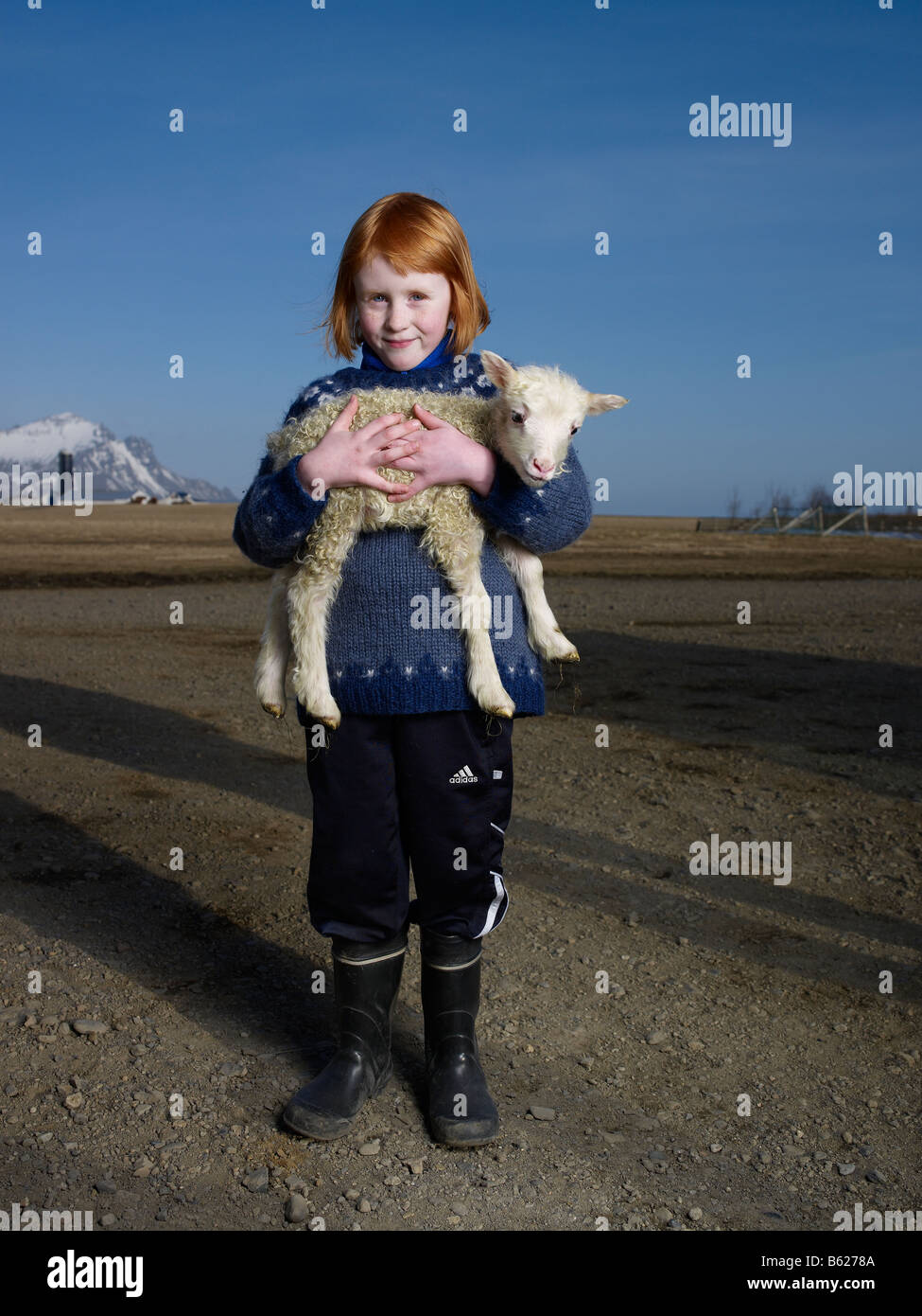 Red headed girl on farm with lamb, Hornafjordur fjord Eastern Iceland - Stock Image