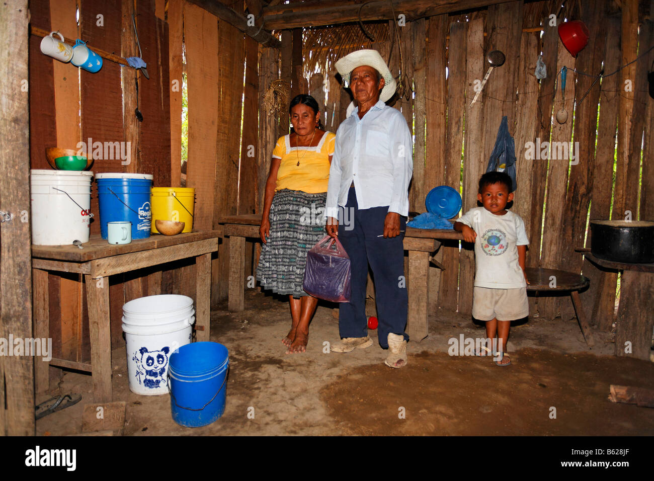 Mayan woman, man, small boy, one-room flat, plastic bucket, wooden hovel, Punta Gorda, Belize, Central America Stock Photo