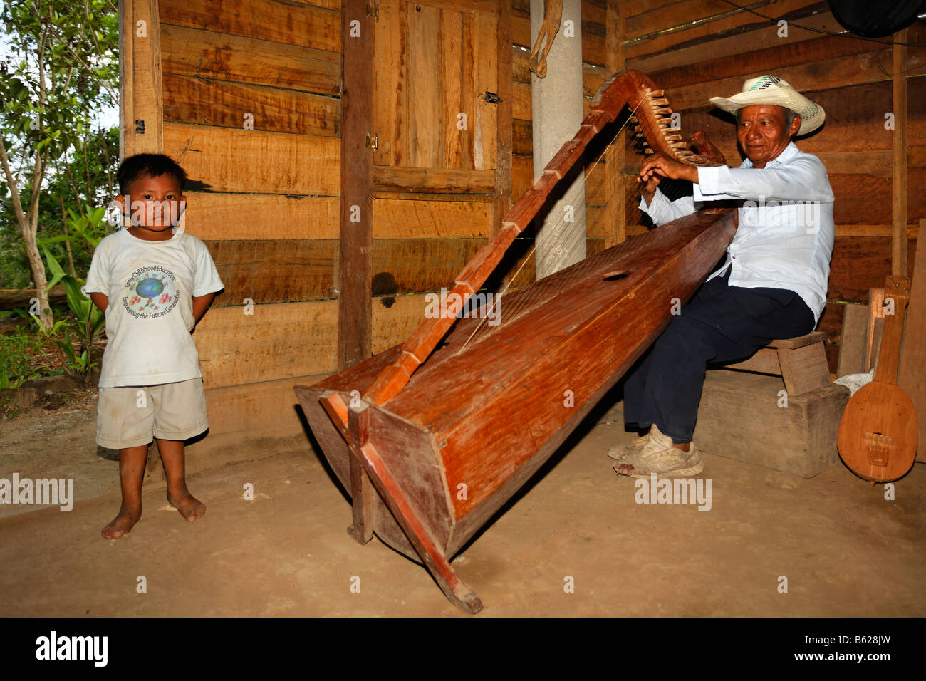 Native musician playing a self-made instrument, harp, small boy, wooden hut, Punta Gorda, Belize, Central America - Stock Image