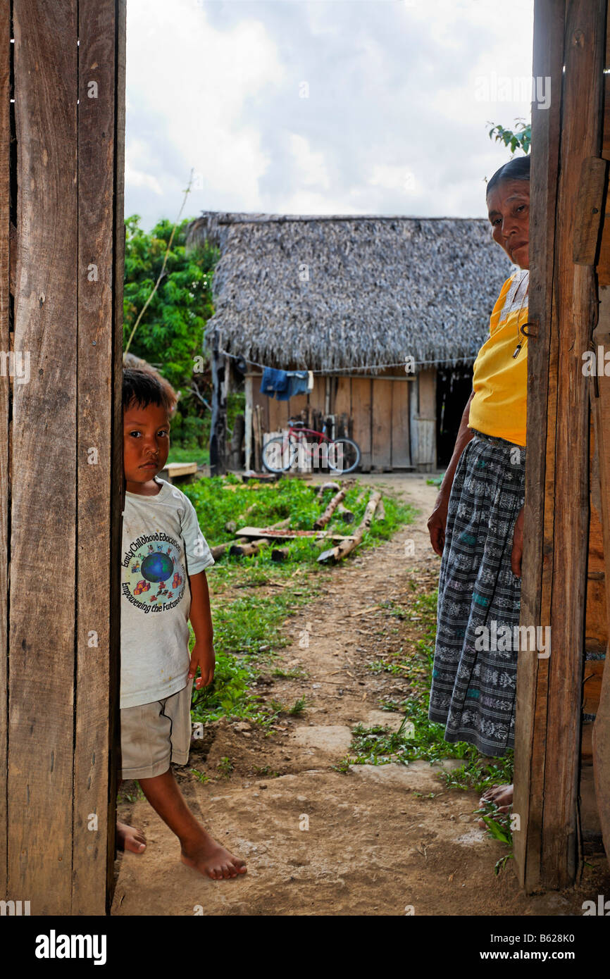 Small boy and a Mayan woman standing in a doorway, hut, Punta Gorda, Belize, Central America Stock Photo