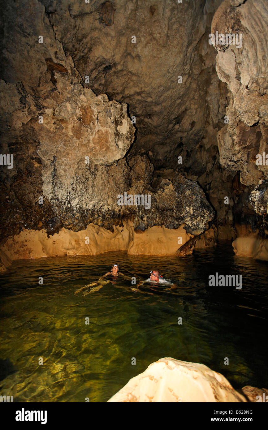 Man and woman with LED lamps on their heads, swimming in warm water investigating a cave, Punta Gorda, Belize, Central - Stock Image