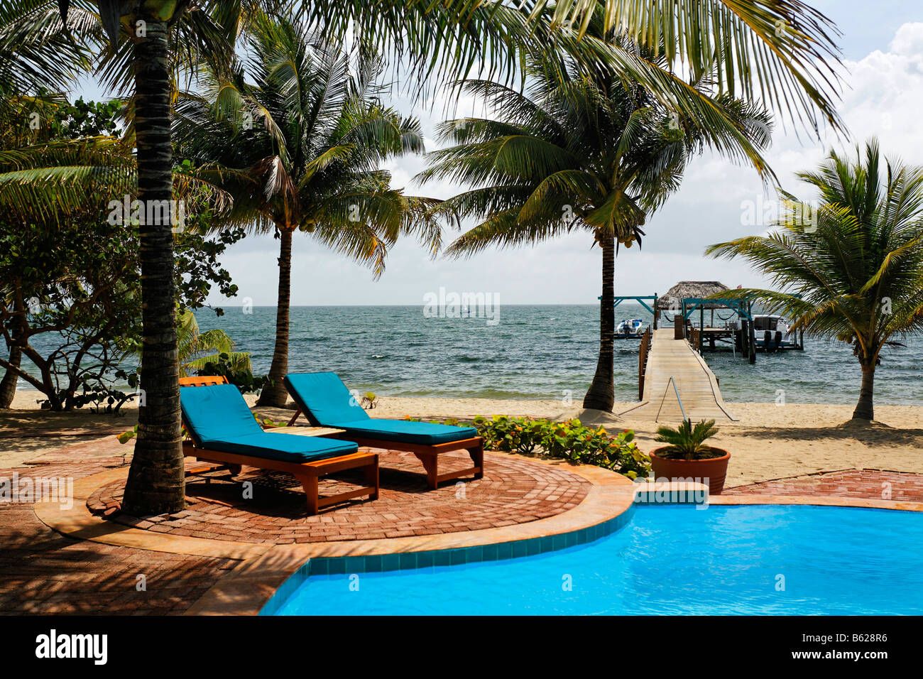 Deckchairs, swimming pool, beach and wharf, Hamanasi Hotel, Hopkins, Dangria, Belize, Central America, Caribbean - Stock Image
