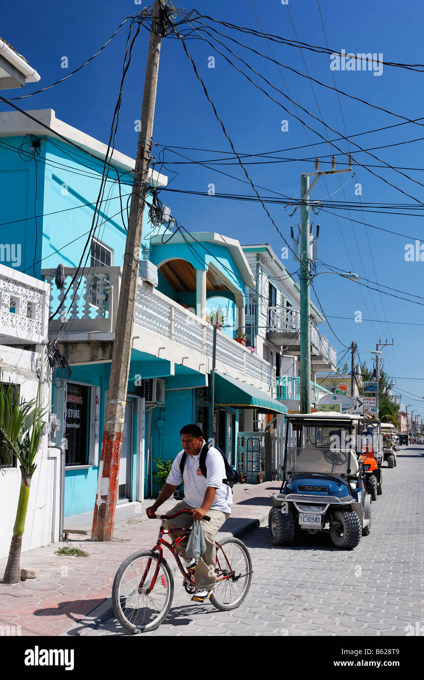 Web of overhead cables on the main street over a bicycle, wooden houses and golf cart, San Pedro, Ambergris Cay - Stock Image