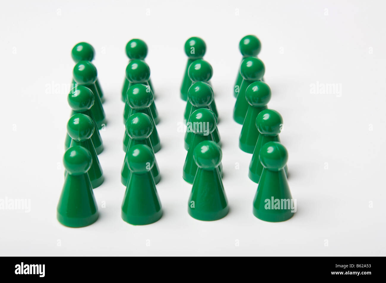 Green gaming pieces standing ordered together, symbolic of in rank and file - Stock Image