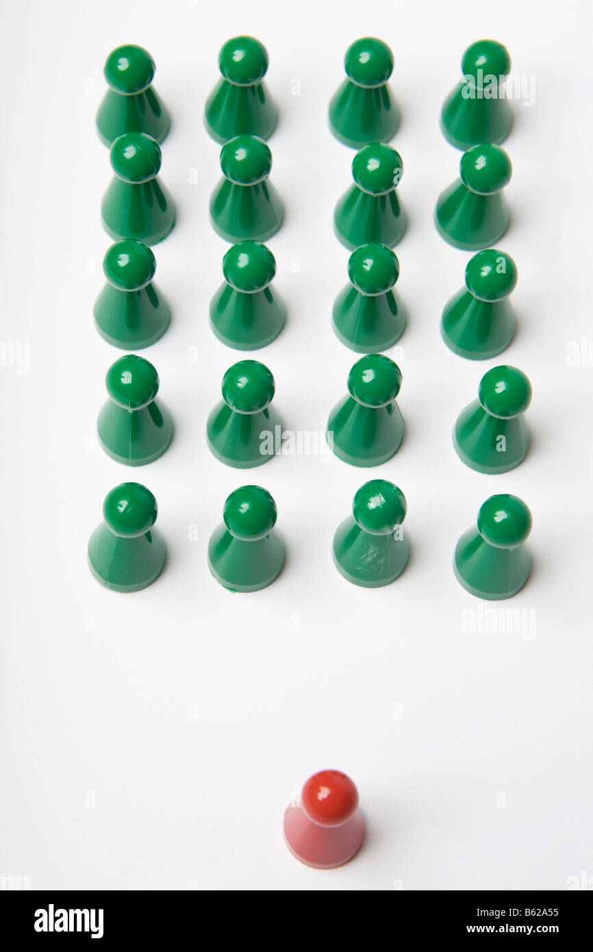Green gaming pieces standing ordered together with a single red gaming piece in front, symbolic of in rank and file - Stock Image