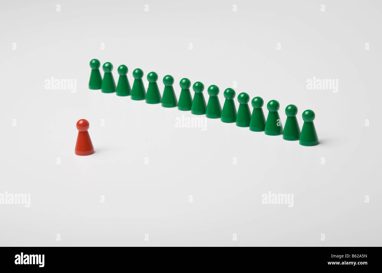 A row of green game pegs facing a single red one, symbol for holding a speech, coaching - Stock Image