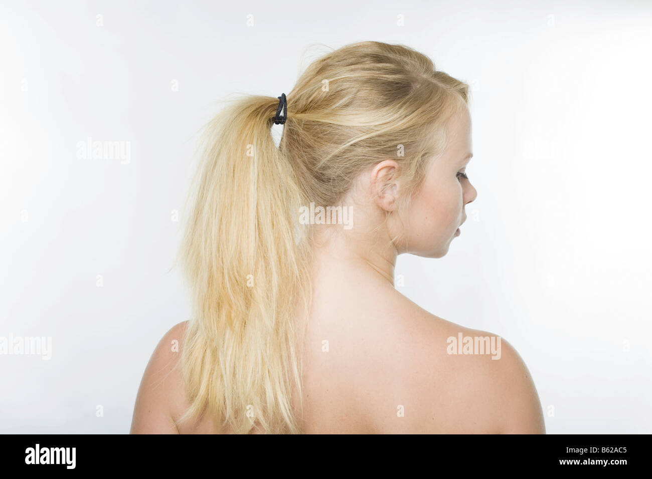 Young woman looking to the side, blonde pony-tail hanging over her shoulders - Stock Image