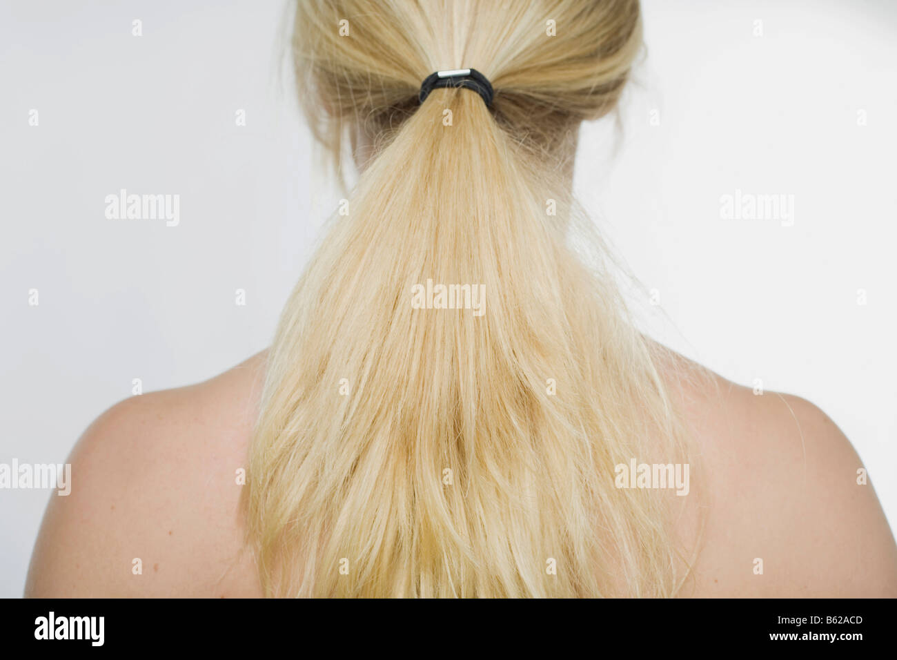 Young woman with a blonde pony-tail hanging over her shoulders - Stock Image