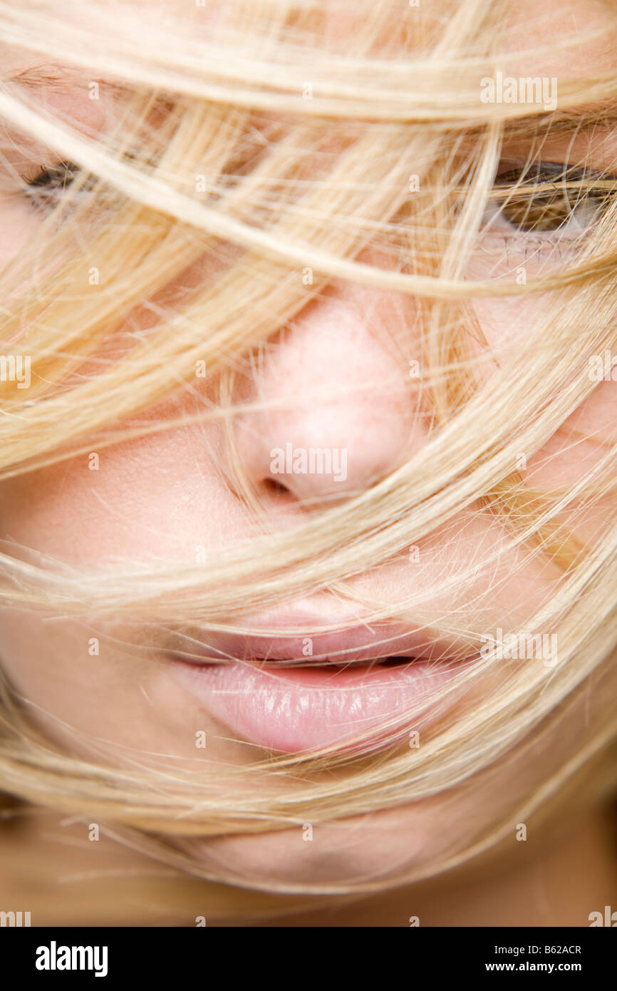 Young blond woman, hair partly covering her face, facial close-up - Stock Image