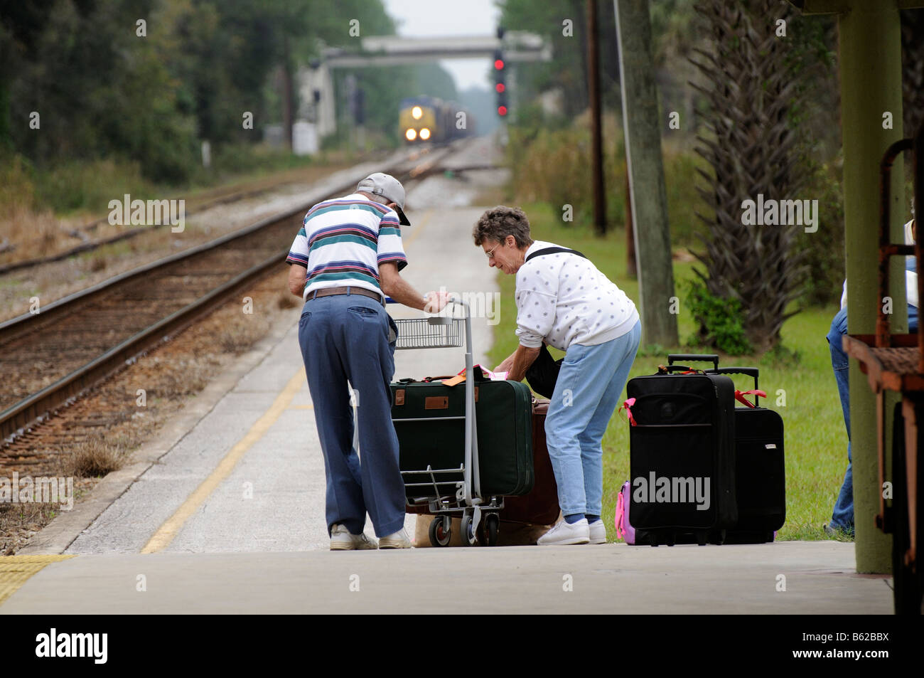 Railroad passengers with luggage trolley and bagage on railroad station platform in Florida USA - Stock Image