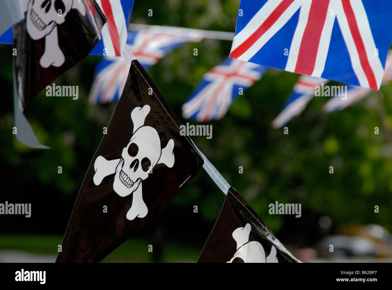 Jolly Roger pirate pennants and Union Jack flags strung up on a narrowboat, Little Venice, London, England Stock Photo