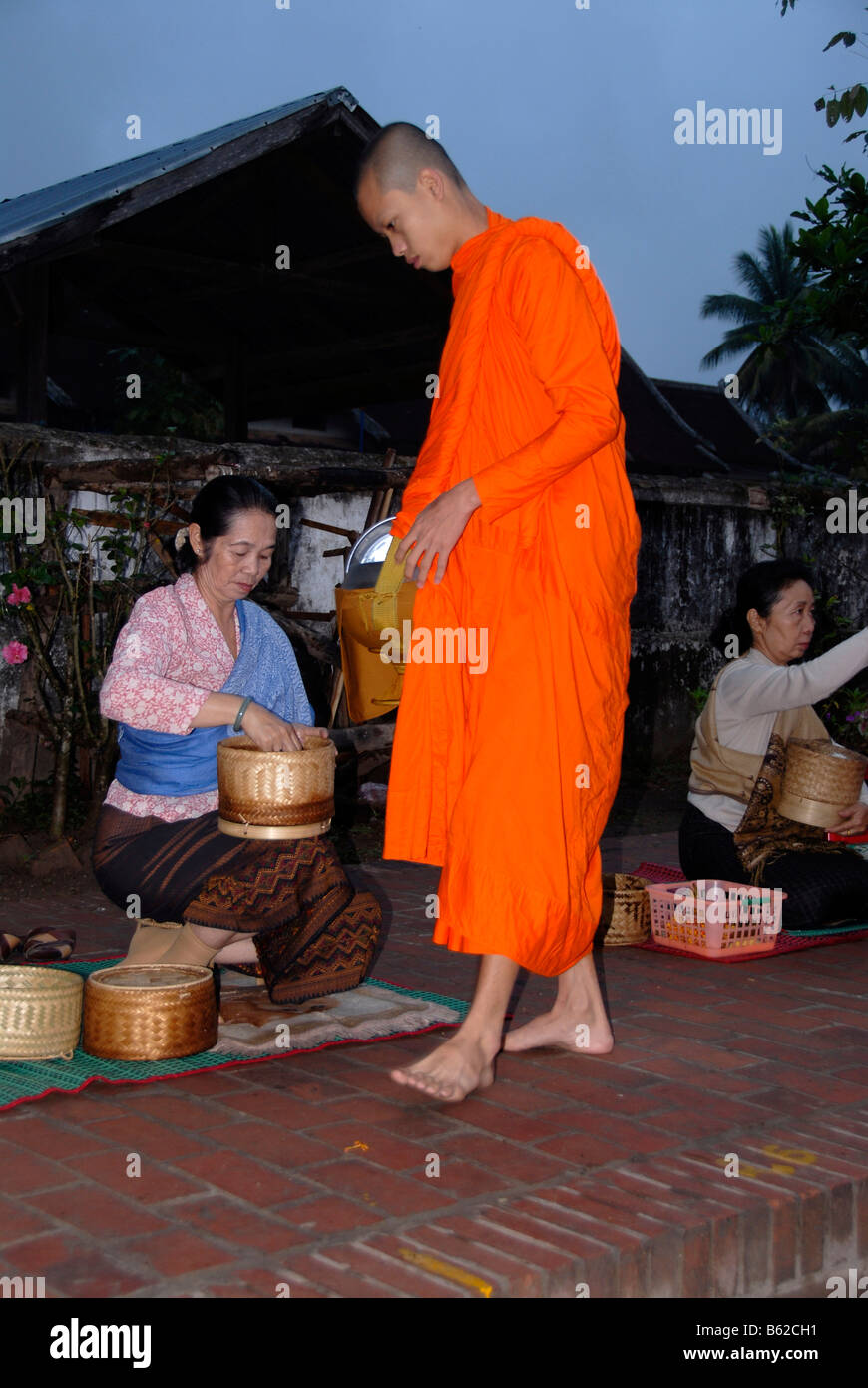 Buddhist monk with begging bowl receiving rice in the morning, Luang Prabang, Laos, Southeast Asia Stock Photo