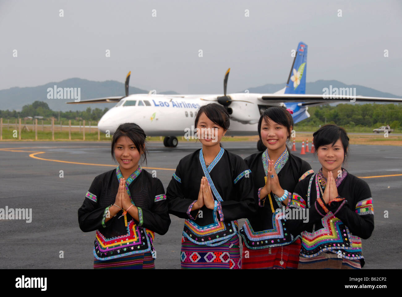 Reception by young Laotians giving the Wei greeting in front of an aircraft of Lao Airlines, Luang Namtha Airport, - Stock Image