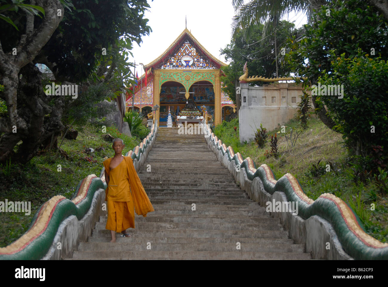 Buddhist monk on the long steps leading to the Wat Jom Khao Manilat temple in Houay Xai, Bokeo Province, Laos, South - Stock Image