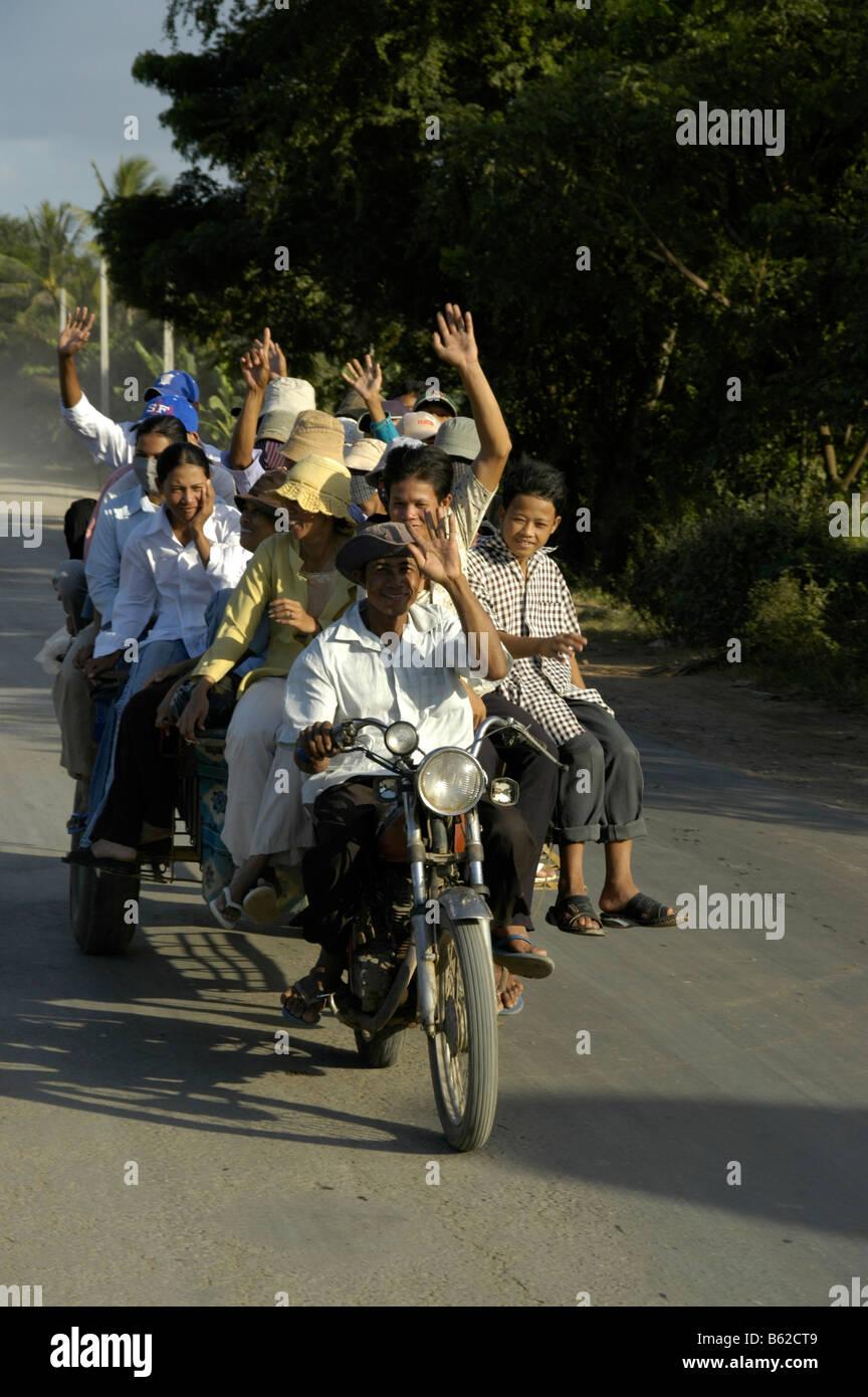 Enthusiastic people traveling on a crammed full motorikshaw, near Phnom Penh, Cambodia, Southeast Asia Stock Photo