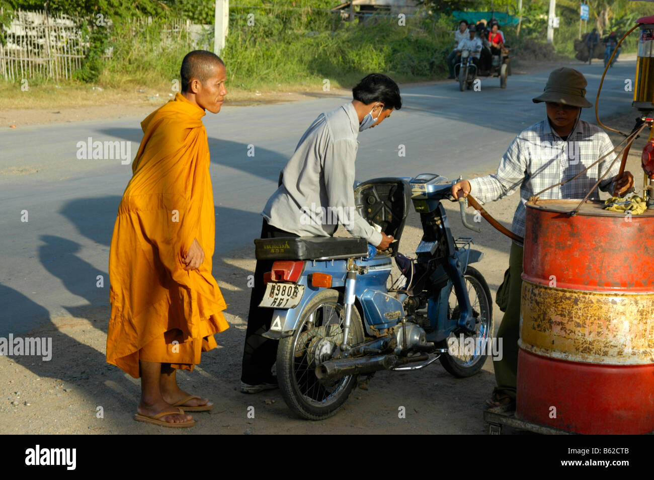 Motocycle driver with a monk at a primitive gas station, near Phnom Penh, Cambodia, Southeast Asia Stock Photo