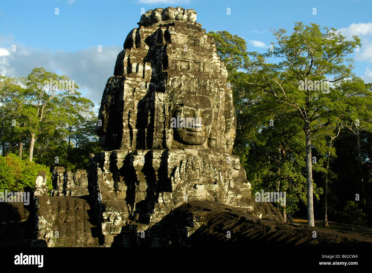 Tower with stone relief of a face, The Bayon Temple in Angkor Thom, with forest, Siem Reap, Cambodia Stock Photo