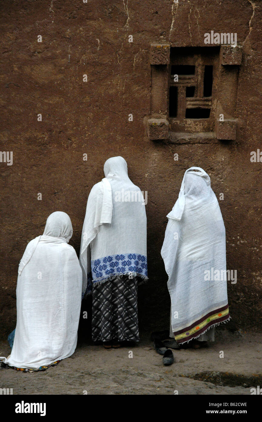Ethiopian orthodox women wearing white capes, praying in front of the wall of the monolithic Beta Medhane Alem Church, - Stock Image