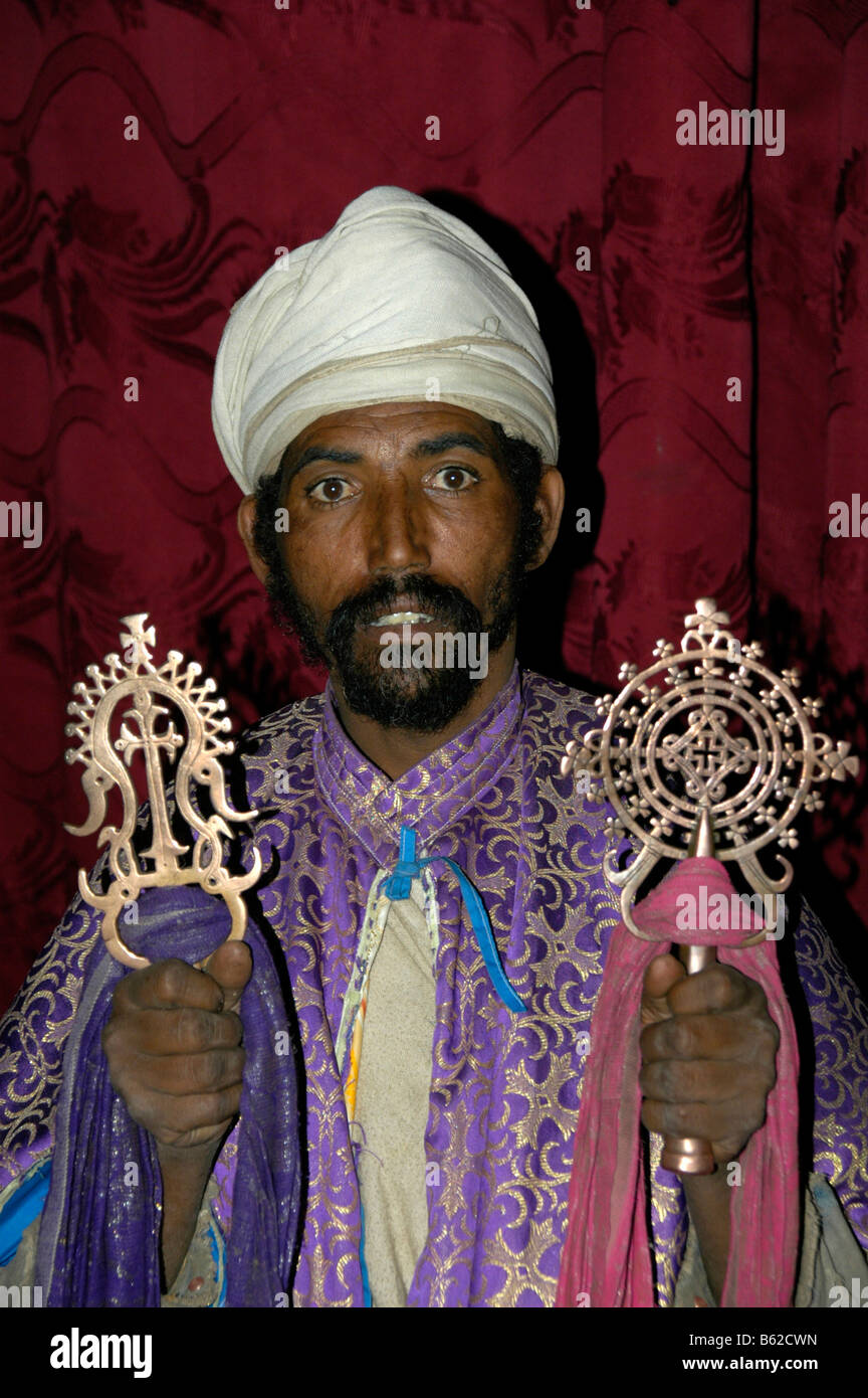 Priest wearing a turban, holding two elaborate candles, monolithic church, Lalibela, Ethiopia, Africa - Stock Image