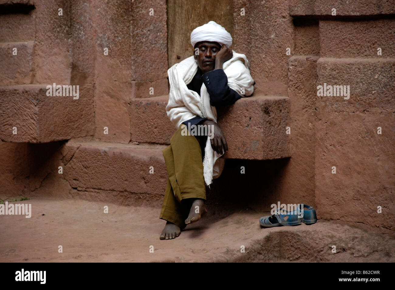 Mann dozing on the steps of a monolithic church, Lalibela, Ethiopia, Africa - Stock Image