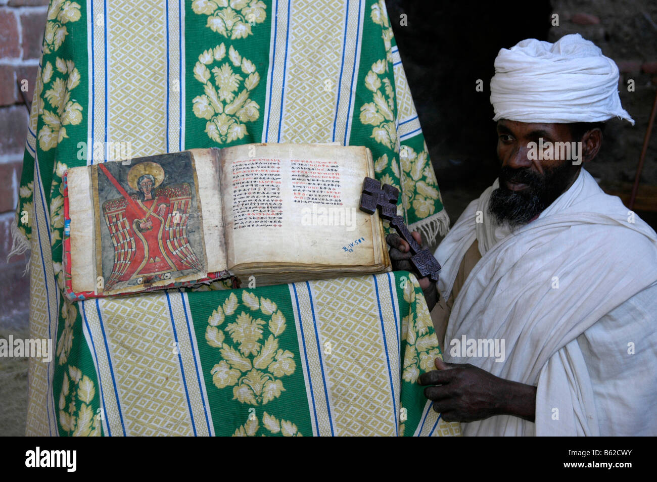 Ethiopian orthodox priest holding old bible with a colourful picture of a saint, monolithic church, Lalibela, Ethiopia, - Stock Image