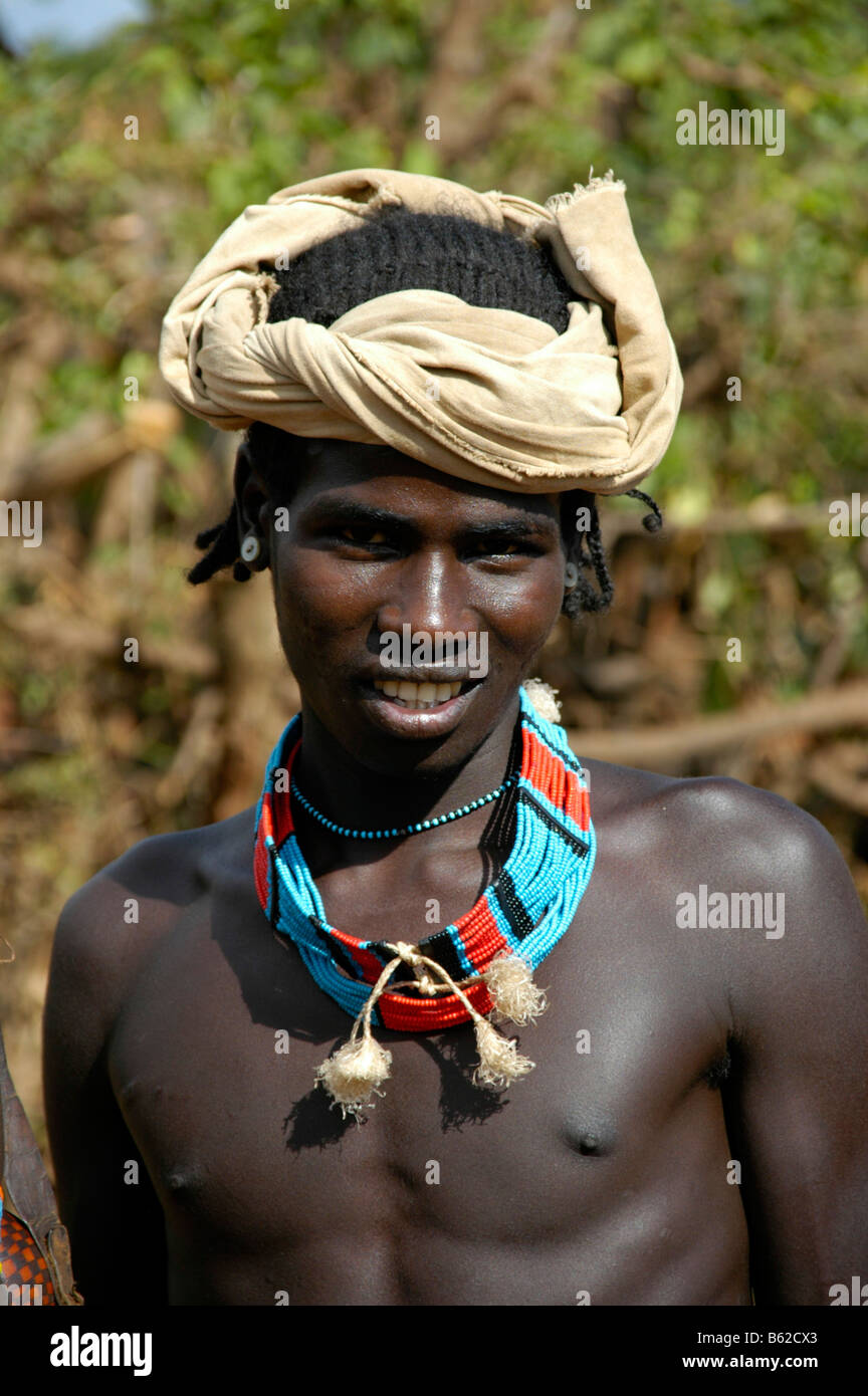 Portrait of a young man with a colourful necklace and a white turban, Keyafer, Ethiopia, Africa - Stock Image
