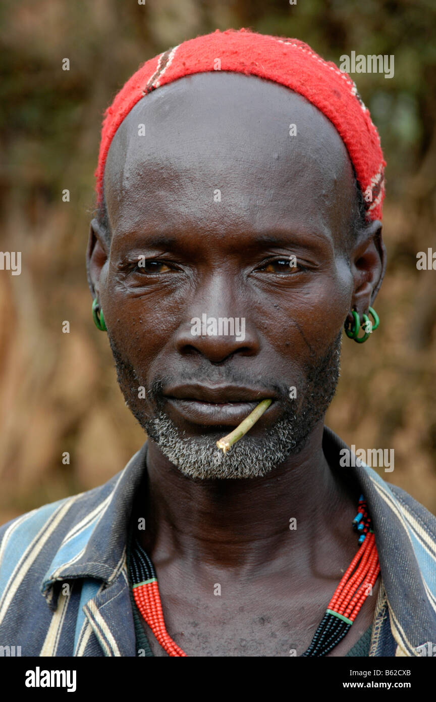 Portrait of a young man with a stick in his mouth, Keyafer, Ethiopia, Africa - Stock Image