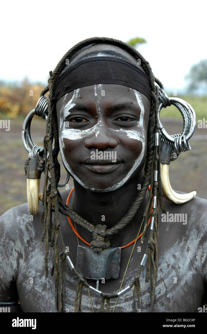 Portrait of a young man from the Mursi tribe, wild, heavy headdress made of teeth of a male boar, near Jinka, Ethiopia, - Stock Image