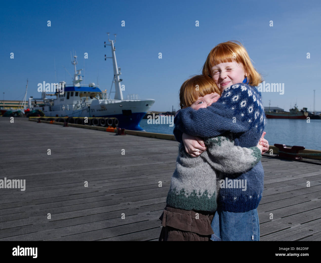 Red headed sisters hugging  at harbor,  Eastern Iceland - Stock Image