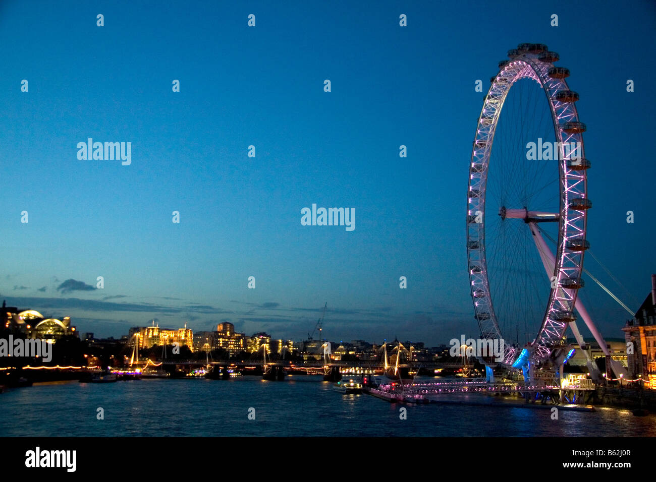 The London Eye at night along the River Thames in London England - Stock Image