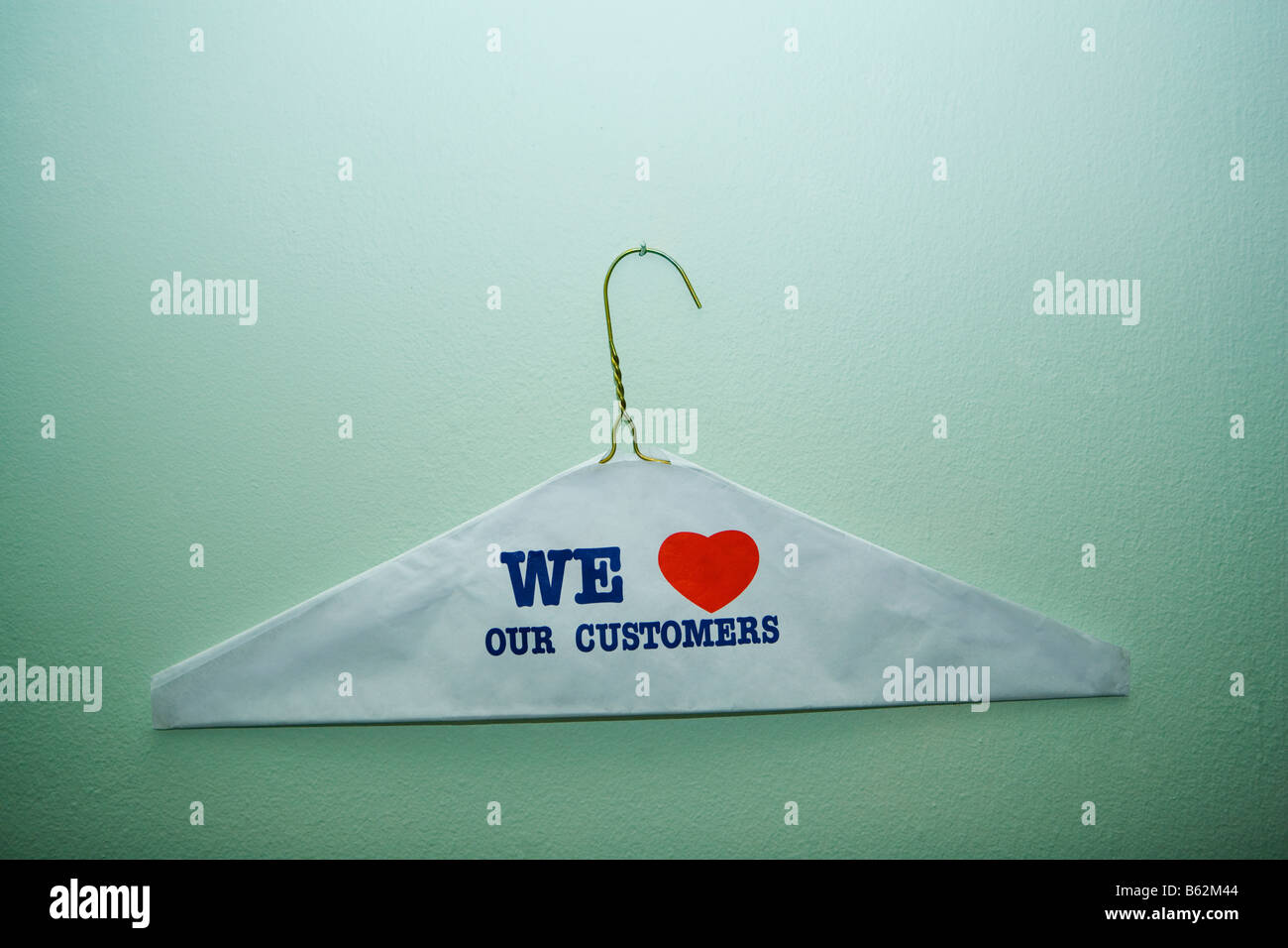 Close-up of text We Love Our Customer painted on a cloth on a hanger, New York City, New York State, USA - Stock Image