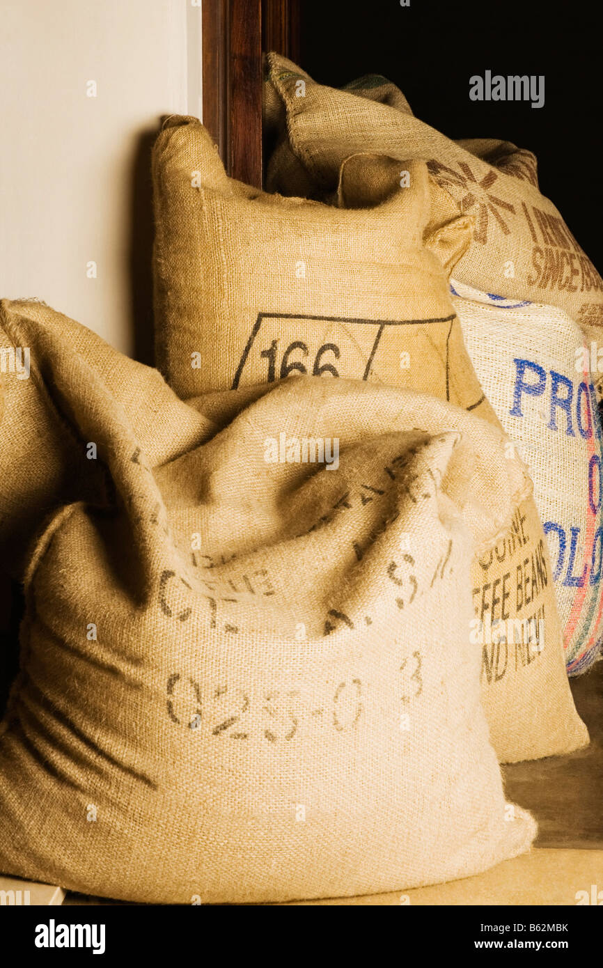 Three sacks of coffee beans in a storage room - Stock Image