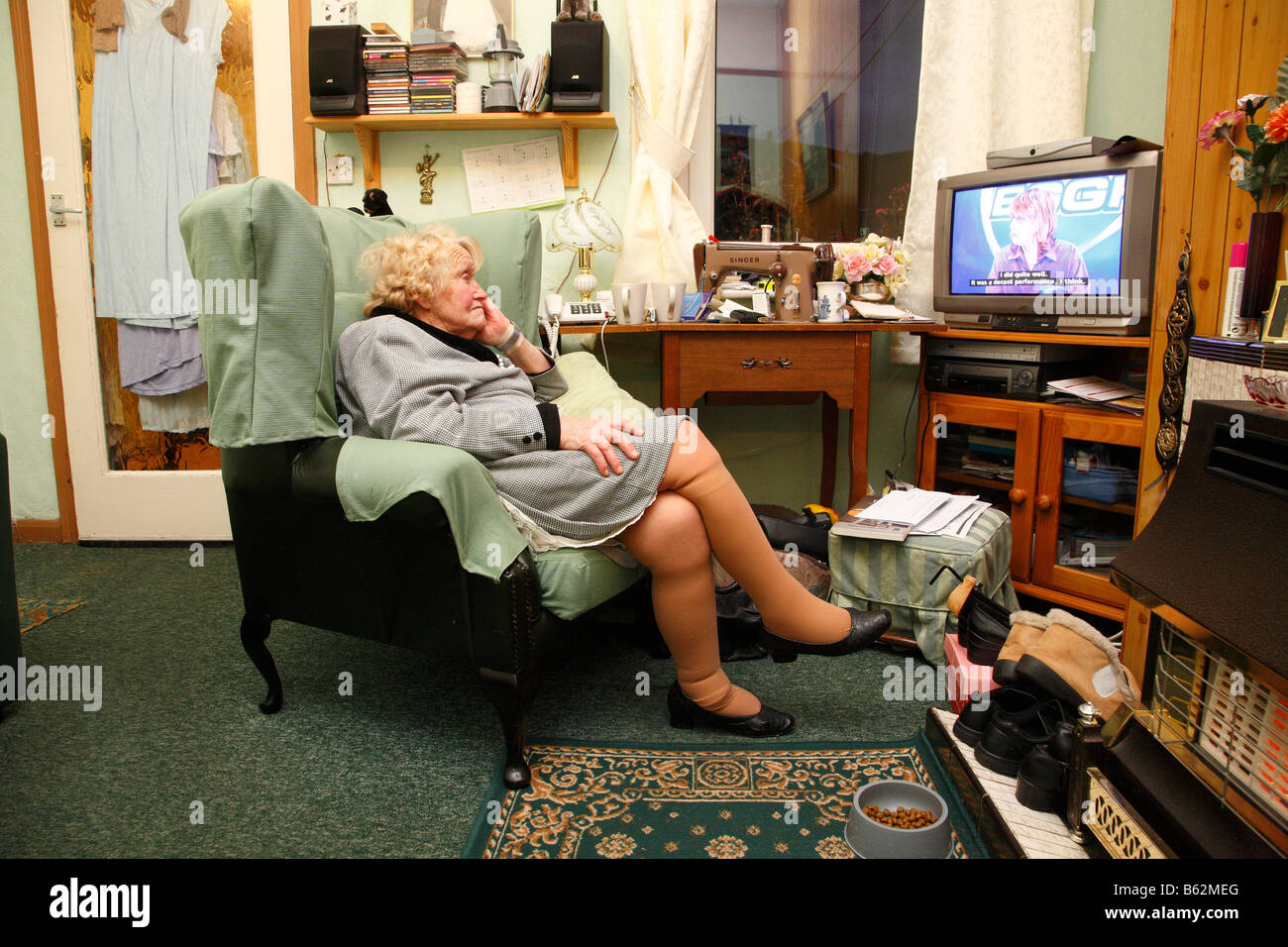 Old woman sitting in a chair watching TV Stock Photo - Alamy