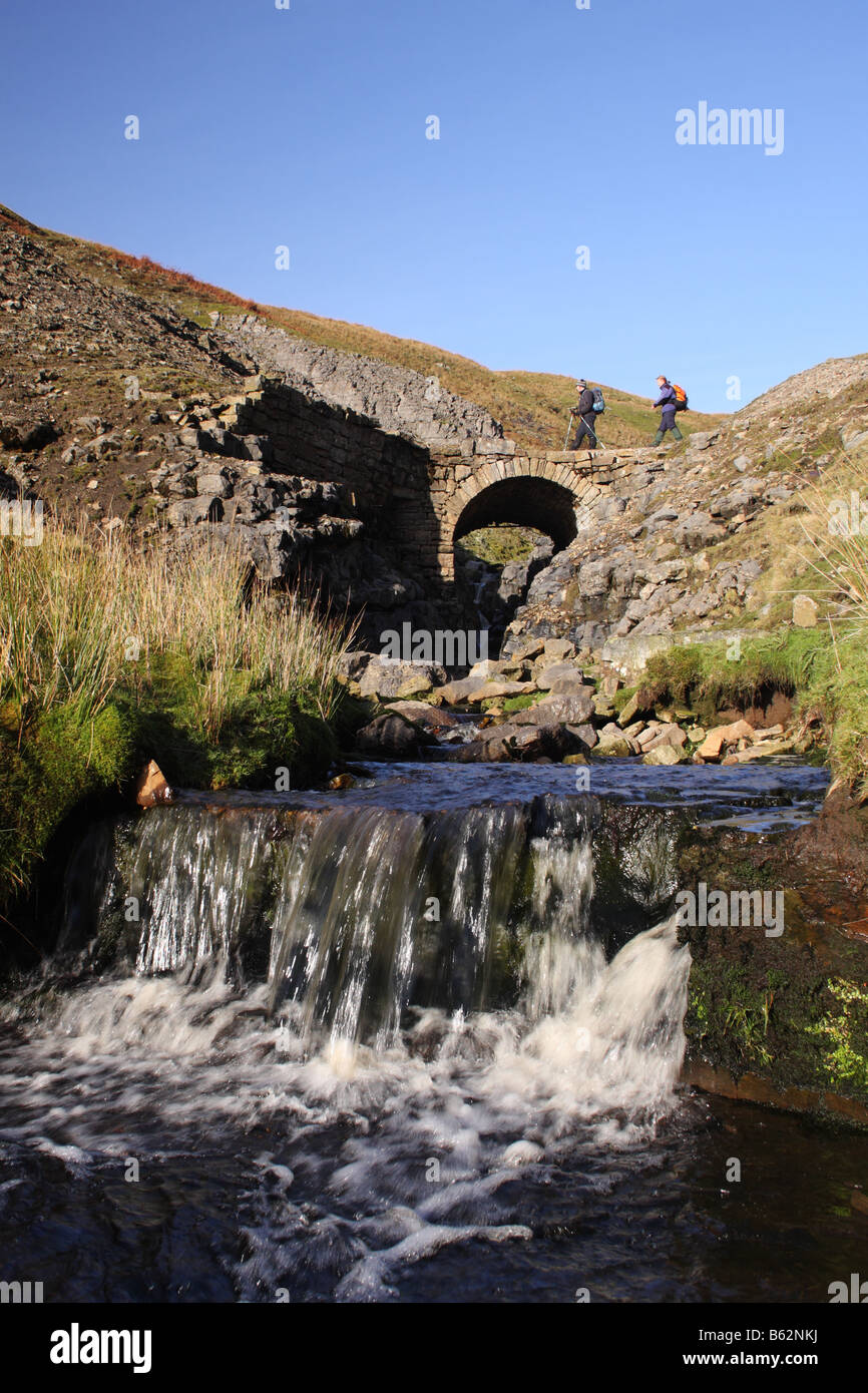 Hill Walkers Crossing Bridge Over Swinner Gill Yorkshire Dales United Kingdom - Stock Image