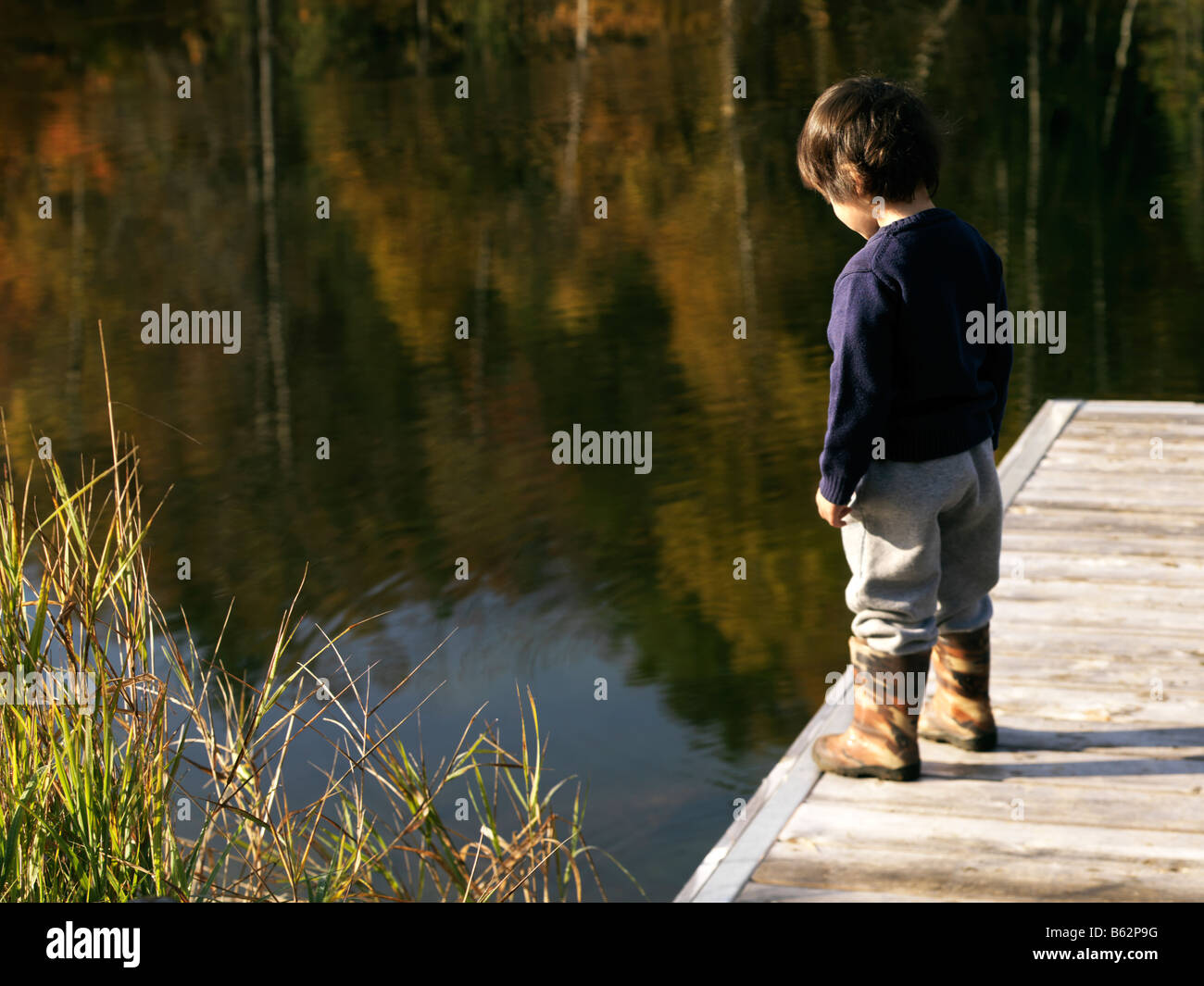 3 year old boy eurasian mix but looks caucasian on a boat dock on a lake with a mountain in the background with - Stock Image