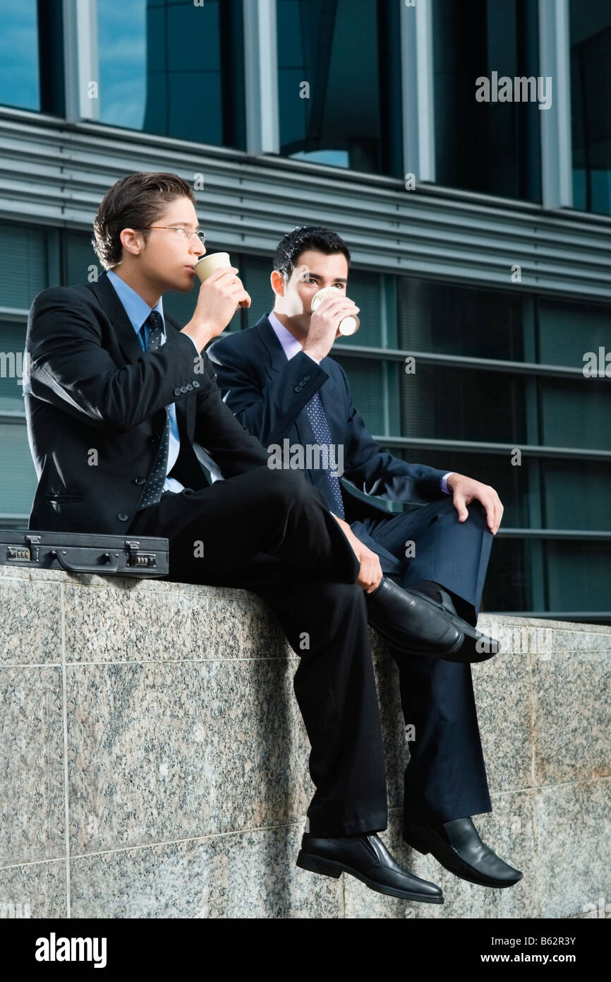 Two businessmen sitting at the edge of a wall and drinking from disposable cups - Stock Image