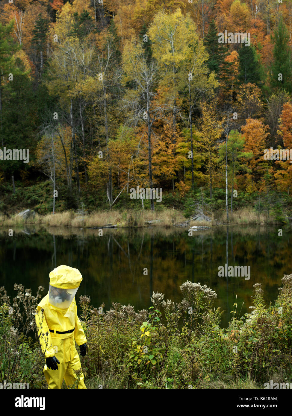 43 year old asian male in a hazmat suit and gas mask outdoors with the fall colours and foliage - Stock Image