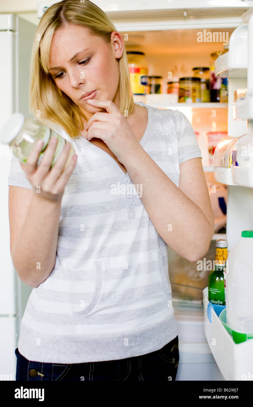 Woman looking at food in fridge - Stock Image
