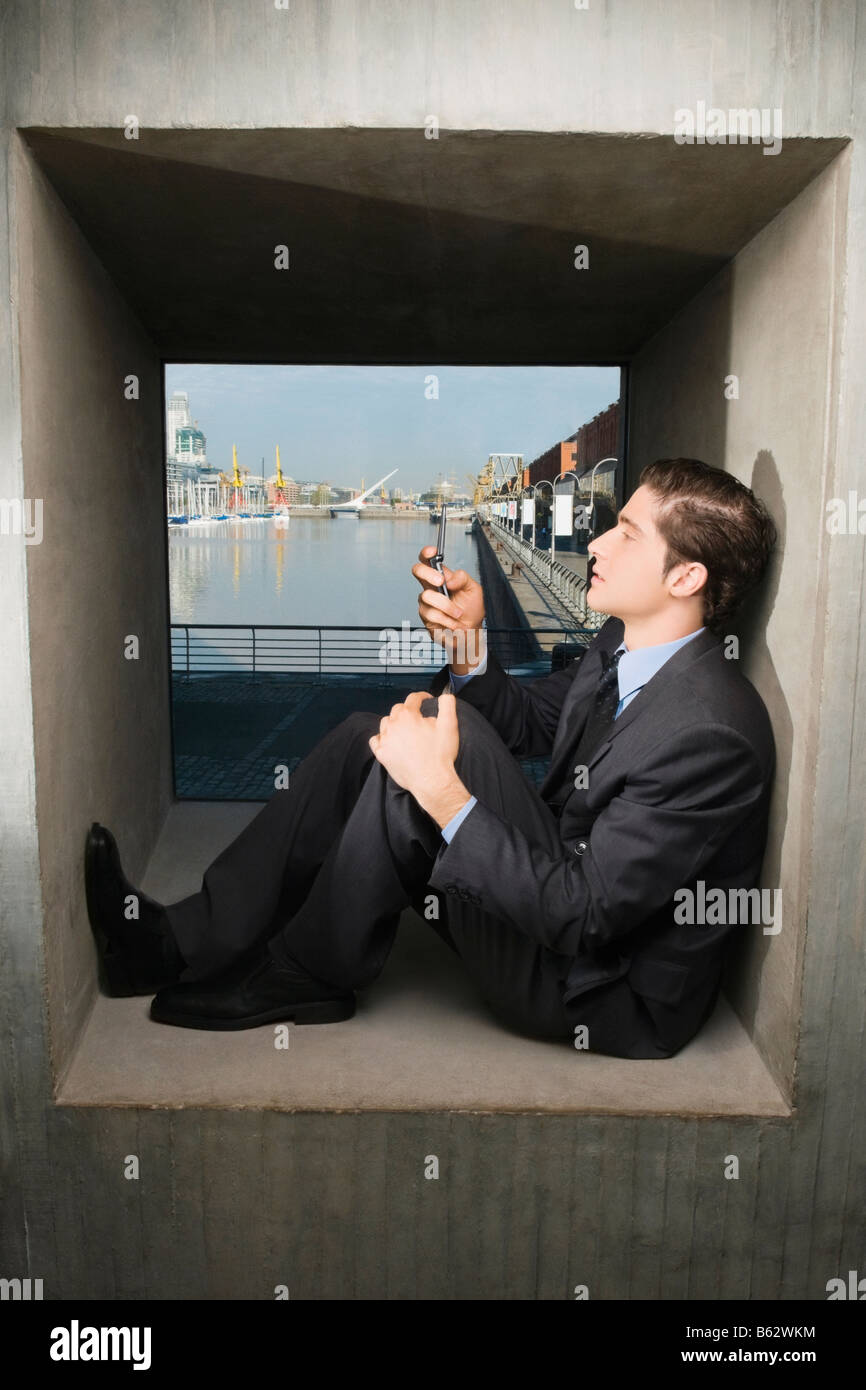Side profile of a businessman sitting on a window sill and operating a mobile phone - Stock Image