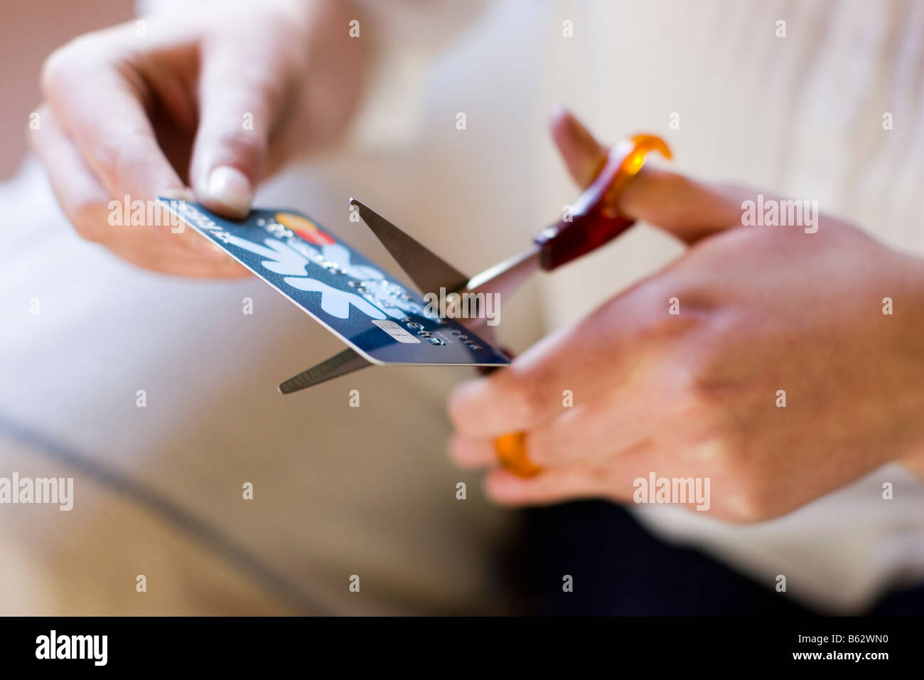 Woman cutting up credit card - Stock Image