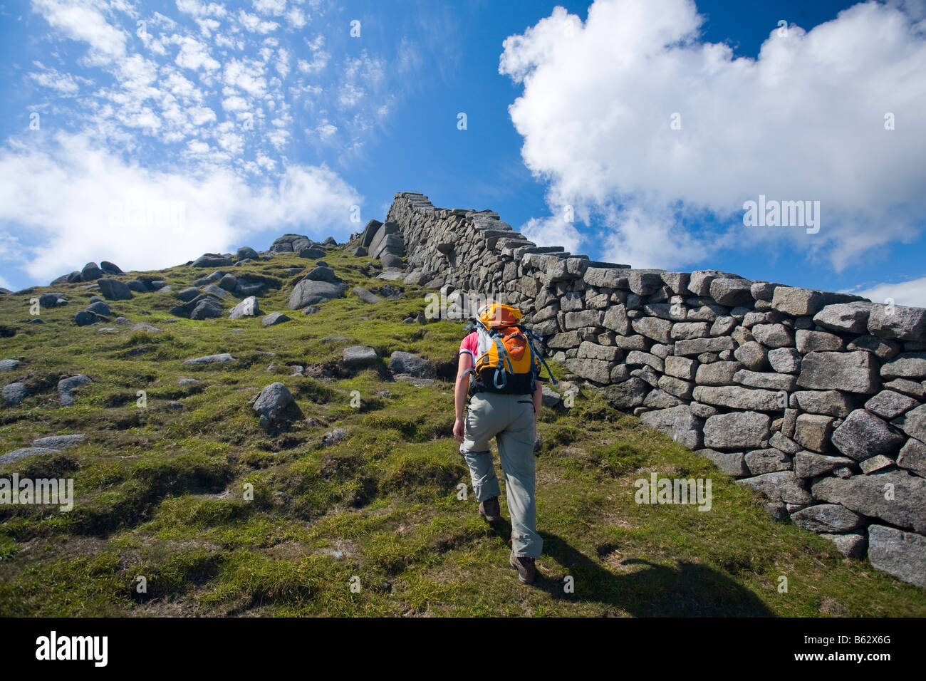 Walker beside the Mourne Wall on the ascent of Slieve Bearnagh, Mourne Mountains, County Down, Northern Ireland, - Stock Image