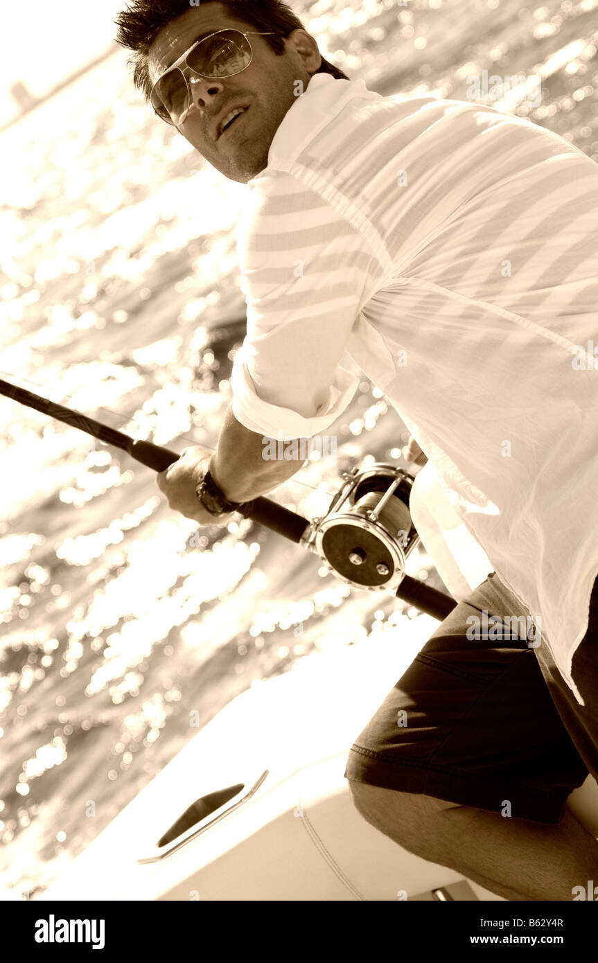 Mid adult man sitting in a boat and fishing Stock Photo