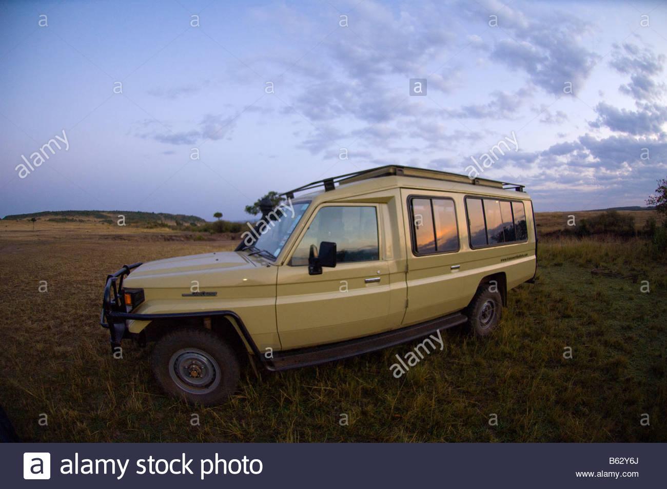 Sunrise reflected into the windows of a safari vehicle Masai Mara National Reserve Kenya - Stock Image