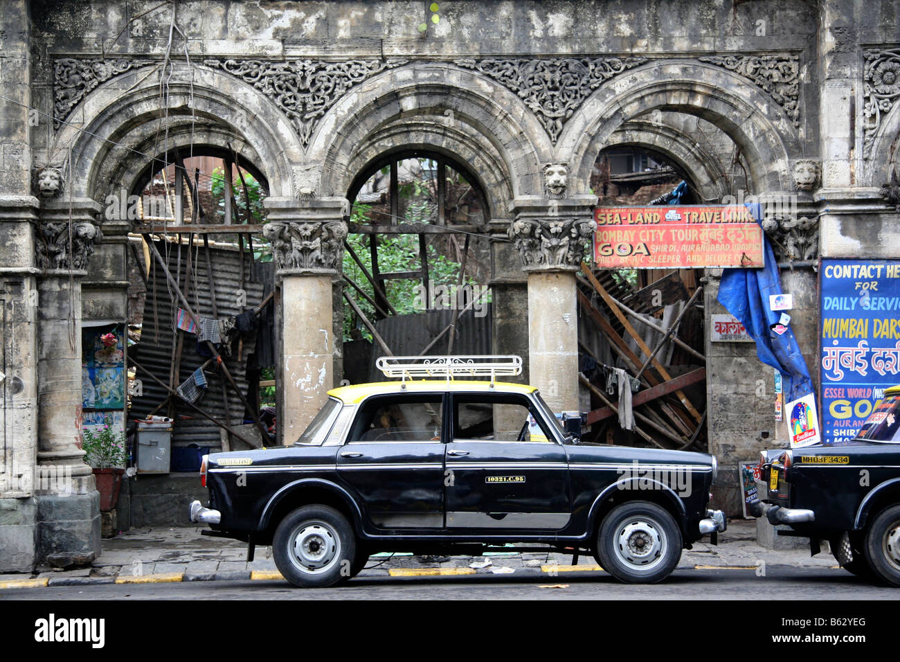 An Ambassador taxi parks on a plot of land being redeveloped next to the Taj Mahal Hotel in Mumbai, India. - Stock Image